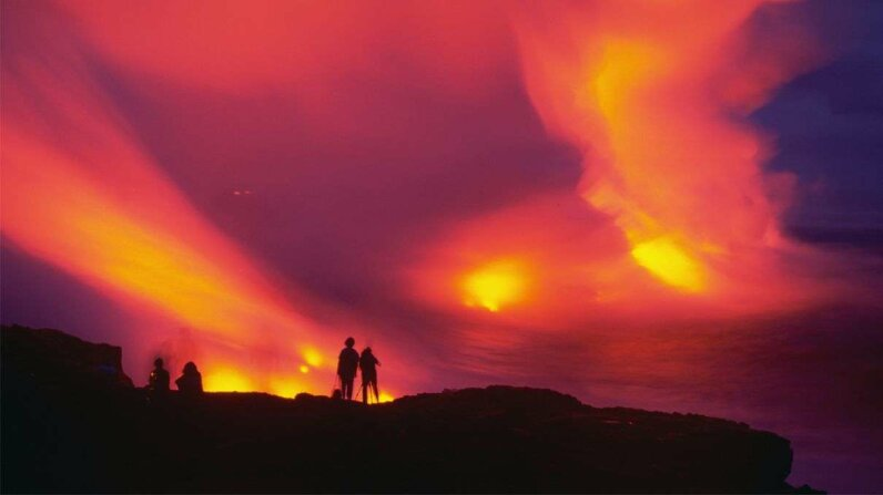 As the sky turns fiery shades of pink and purple, visitors watch the lava flowing into the ocean from the eruption of Kilauea, a volcanic crater in Hawaii Volcanoes National Park. Douglas Peebles/Corbis via Getty Images