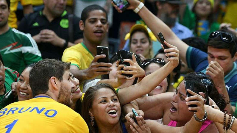 Supporters take selfies with Brazil's Bruno Mossa De Rezende after his team won the men's qualifying volleyball match between Brazil and Mexico at the Rio Olympics, 2016. Yep, they seem to be enjoying their experience. JOHANNES EISELE/AFP/Getty Images