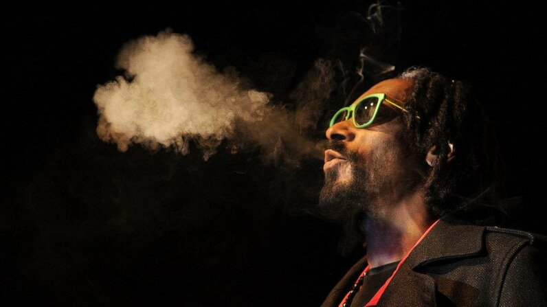 Rapper Snoop Dogg blowing heart-shaped marijuana smoke at a 2013 convention. The musician recently launched a name-brand line of marijuana and other weed-adjacent products. Seth McConnell/Getty Images