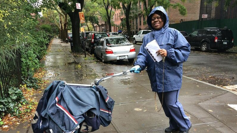 """A letter carrier pushes her mail cart through Brooklyn on a rainy day. You know what they say: """"Neither snow nor rain ..."""" Keith Getter/Getty Images"""