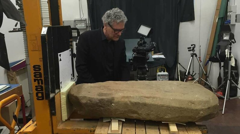 Gregory Warden, co-director and principal investigator of the Mugello Valley Archaeological Project, examines the Etruscan stone slab. Mugello Valley Project