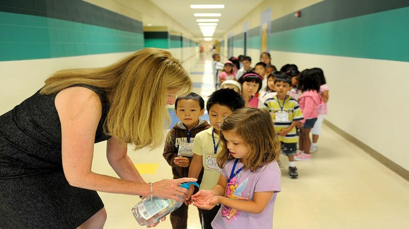 Kindergartners line up with their hands out to get a squirt of hand sanitizer before going into the cafeteria. Katherine Frey/The Washington Post/Getty Images