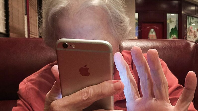 An 80-year-old using her smartphone to check in with friends and family. Many seniors are becoming addicted to their smartphones. Jonathan Nutt/Getty Images