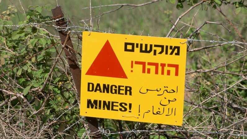 In the Golan Heights, a sign written in English, Hebrew, and Arabic warns of land mines. Richard T. Nowitz/Getty Images