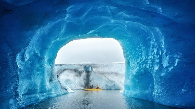 People kayak past a cave inside Valdez Glacier in Alaska. Piriya Wongkongkathep/Moment/Getty Images
