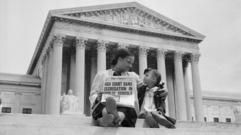 Nettie Hunt sits on the steps of the U.S. Supreme Court with her daughter Nickie, holding a newspaper declaring the Brown v. Board decision to overturn segregation in schools. Bettmann /Getty Images