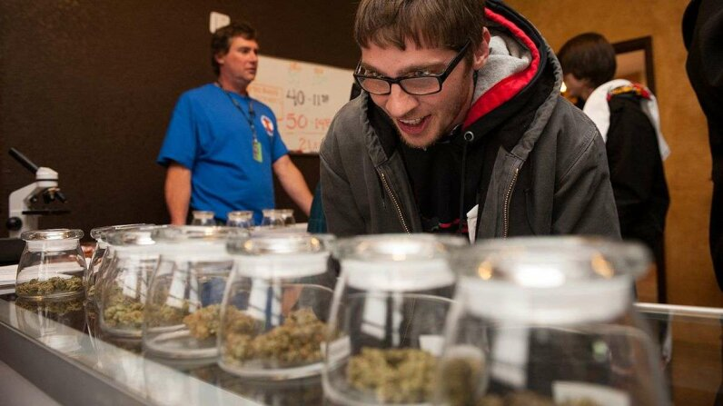 Ohio resident Tyler Williams selects marijuana strains to purchase at a Denver, Colorado, dispensary on Jan. 1, 2014, the first day recreational marijuana use was legally allowed under state law. Theo Stroomer/Getty Images