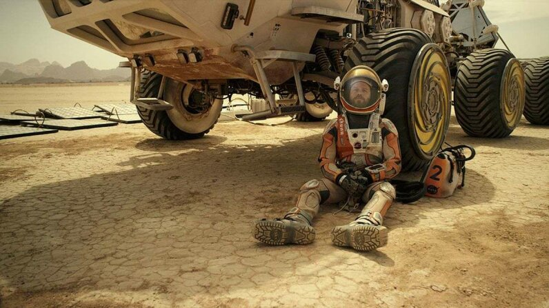 Matt Damon portrays Mark Watney in the film adaptation of 'The Martian.' In the film, he struggles to repair his spacesuit. Twentieth Century Fox