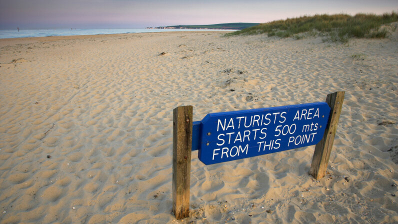 A sign alerts beachgoers in Dorset, England, that a nude beach lies ahead. Oxford Scientific/Getty Images
