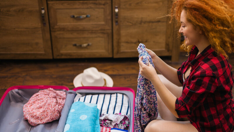 Beautiful young girl with long red curly hair packing suitcase for a holiday.
