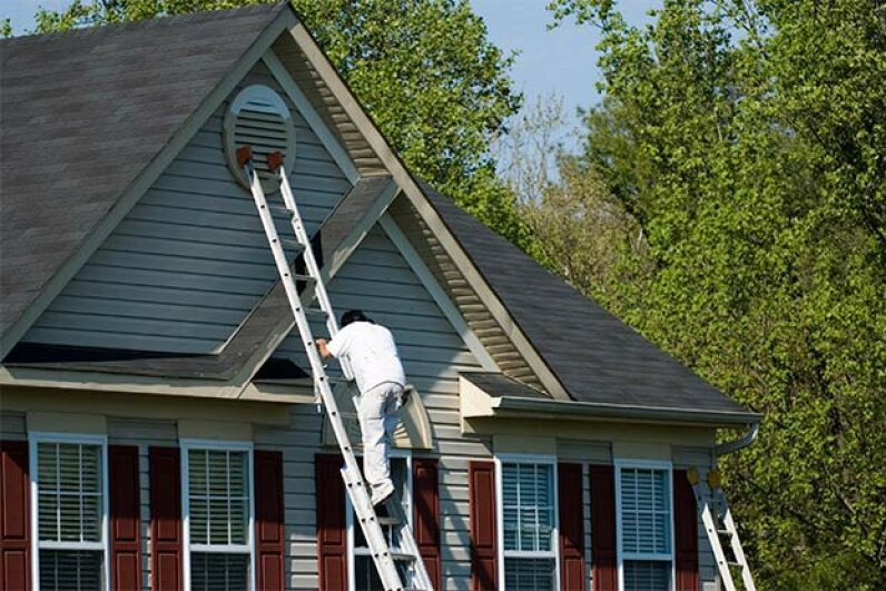 If you're painting the roof eaves, the ladder should extend 1 to 3 feet above the roof. Brian McEntire/iStock/Thinkstock