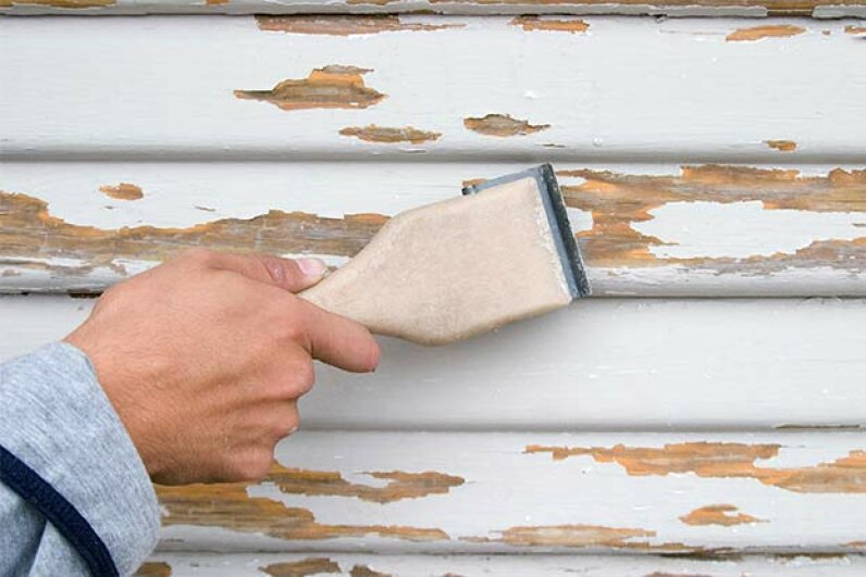 Use a putty knife to remove loose or peeling paint from your surface. Paul Hart/iStock/Thinkstock