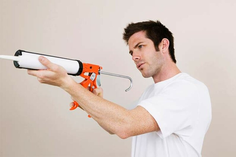 If you're using a manual caulk gun, look for one that has a smooth rod, which offers more control than its ratcheted counterpart. Purestock/Thinkstock