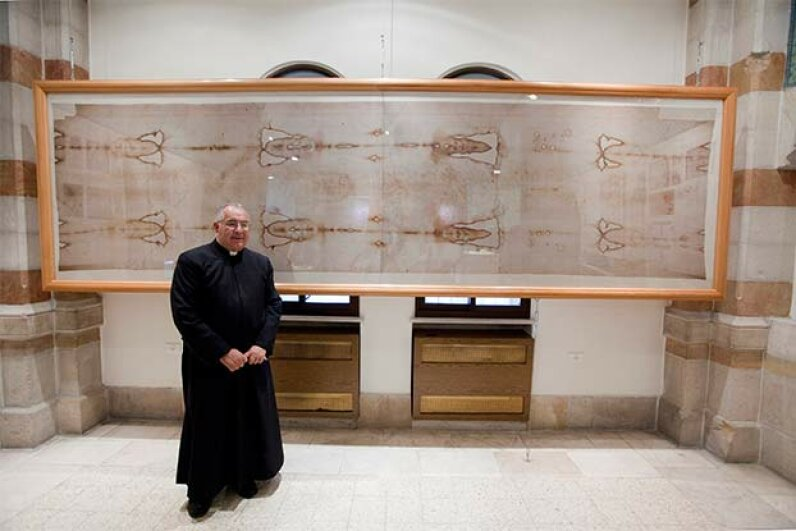 Roman Catholic Father Christopher stands in front of a replica of the Shroud of Turin in the Notre Dame de France Hospice, Jerusalem. Independent Picture Service/UIG via Getty Images)