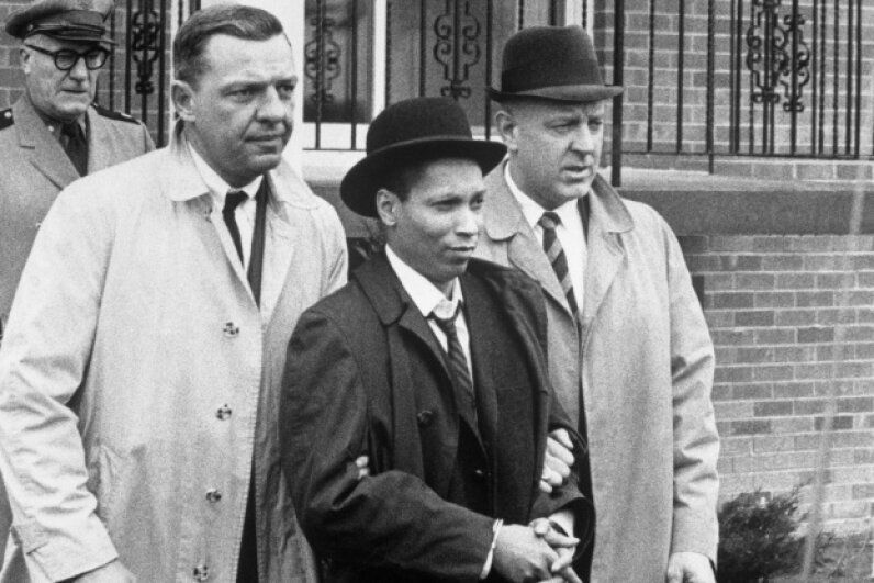 Kitty Genovese's killer, Winston Moseley, is led away in handcuffs on March 21, 1968, after escaping police custody while serving a life sentence for her death. © Corbis