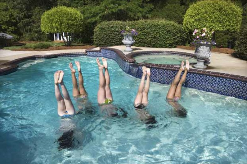 While you need skill to do a handstand on land, anyone can do it in the water. Comstock/Thinkstock