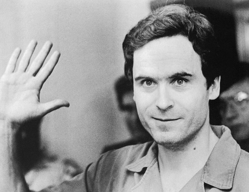 Ted Bundy waves to TV cameras as his indictment for the murders of Florida State University students Lisa Levy and Margaret Bowman is read at the Leon County Jail in Florida. Hulton-DeutschCollection/UniversalHistoryArchive/GettyImages