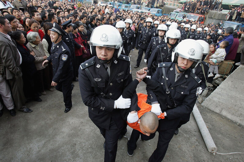 Chinese police escort a convicted murderer to a public sentencing on Nov. 17, 2004 in Chongqing, China. More than 10,000 watched. China Photos/Getty Images