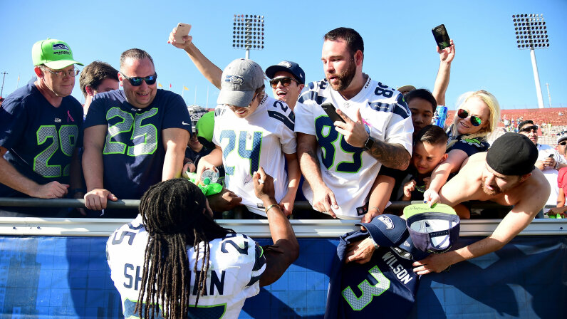 Richard Sherman (No. 25) of the Seattle Seahawks signs autographs for fans after a 16-10 win over the Los Angeles Rams at Los Angeles Memorial Coliseum on Oct. 8, 2017.   Harry How/Getty Images