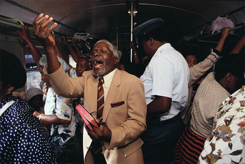 A preacher holds an impromptu service on a train going between Soweto and Johannesburg. © Gideon Mendel/Corbis