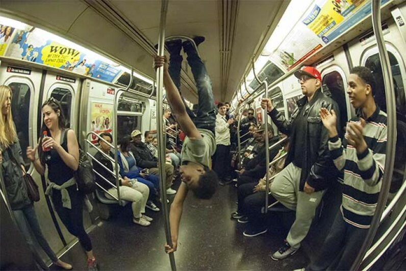 An acrobat busts some moves for subway riders in New York. As part of NYPD Police Commissioner Bill Bratton's crack-down on quality of life offenses, arrests of these performers quadrupled to 240 in July 2014, as compared to the same time in 2013. © Richard Levine/Demotix/Corbis