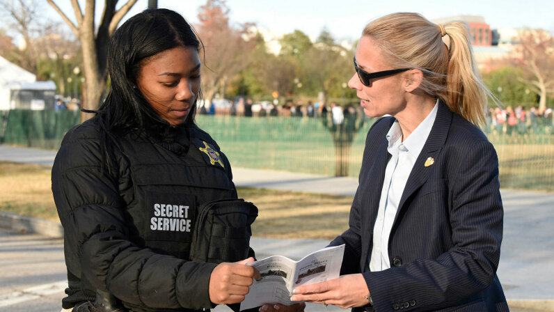 Two female Secret Service agents confer at the 2016 National Tree Lighting ceremony in Washington, D.C. Secret Service