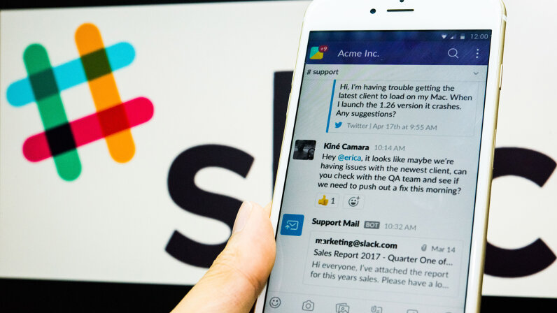 Young man uses Slack on his iPhone