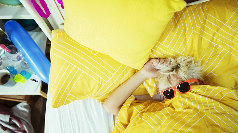 woman lying on yellow comforter, wearing sunglasses