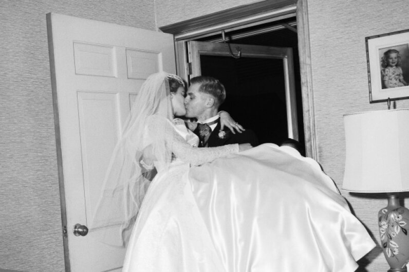 Now, carrying the bride across the threshold is a romantic gesture, rather than a way to ward off evil spirits.  © Bettmann/CORBIS