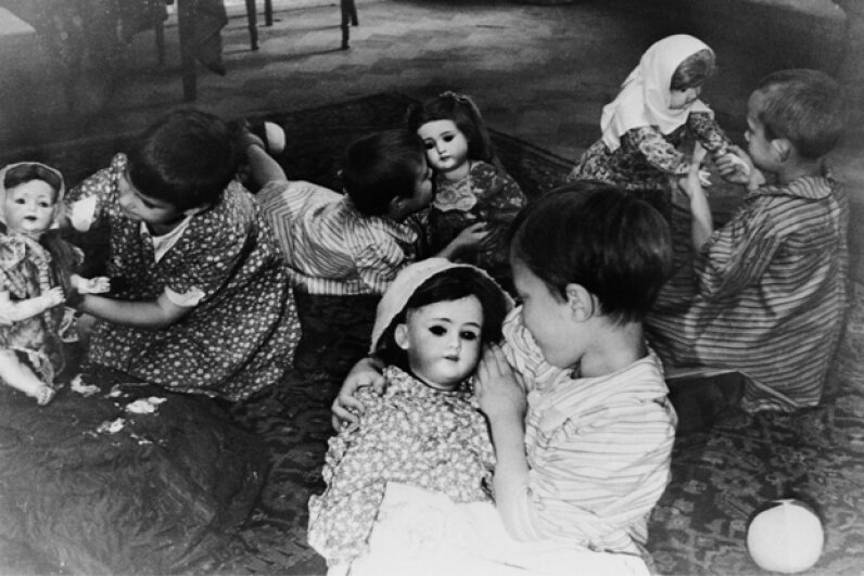 Lifelike dolls hold the interest of four Russian orphans whose parents were killed in the Leningrad siege. When the picture was taken on Jan. 15, 1946, the kids were being cared for in a children's home. © Bettmann/Corbis