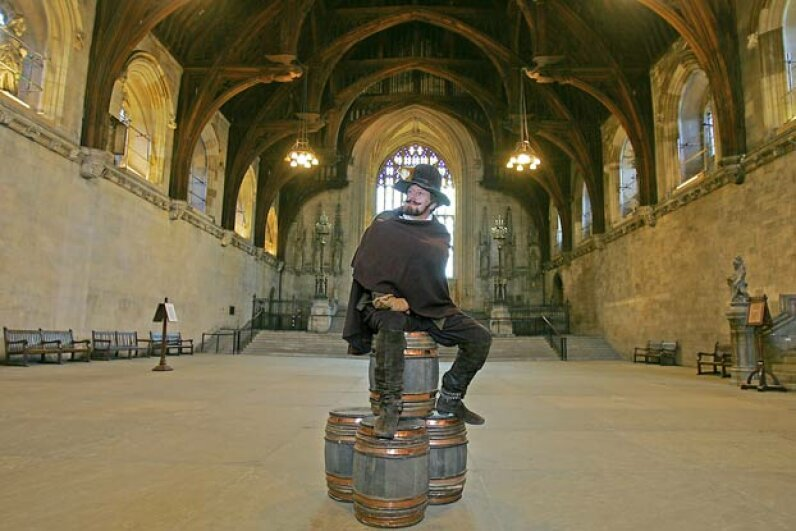 An actor dressed as Guy Fawkes sits atop fake barrels of gunpowder in Westminster Hall in the Houses of Parliament in London, as the British Parliament marked the 400th anniversary of the discovery of the Gunpowder Plot in 2005. ODD ANDERSEN/AFP/Getty Images