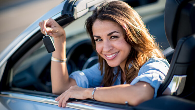 Woman holding car keys in hand in car