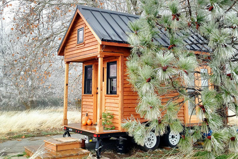 A tiny house sits next to a pine tree. Tammy Strobel Used Under Creative Commons CC By 2.0 License
