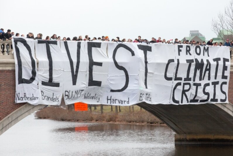 """A """"Divest from climate change"""" banner is dropped over the Charles River by Boston students who aim to stop climate change by having their schools divest from the fossil fuel industry. Around 150 students from Boston area colleges and universities rallied on Dec. 8, 2013. © Paul Weiskel/Demotix/Corbis"""