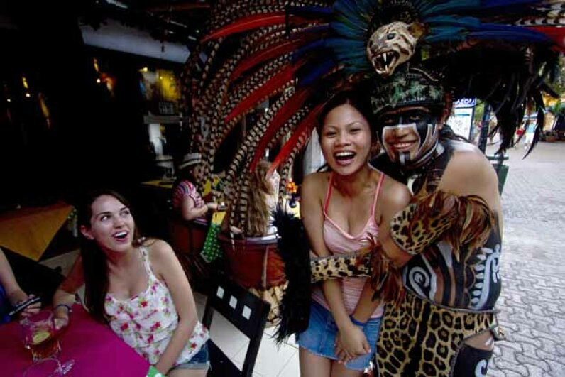 Canadian tourists pose for a pic with a Mexican man wearing a pre-Hispanic costume at a tourist area of Playa del Carmen. Pedro PARDO/AFP/Getty Images