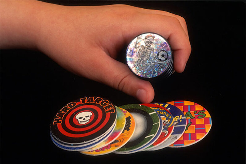 Players contribute an equal number of pogs to build a stack with the pieces face-down, taking turns throwing their slammers onto the stack top, causing it to spring and the pogs to scatter. Players keep any pogs landing face-up after they're thrown. Yvonne Hemsey/Getty Images