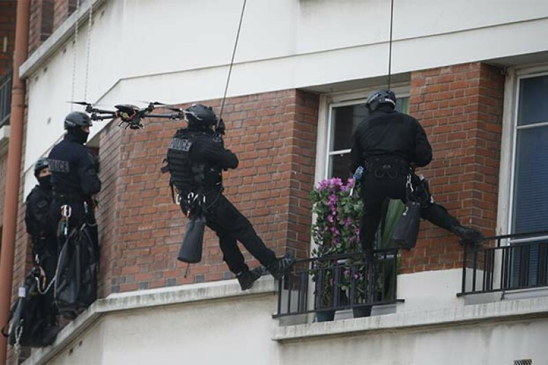 Members of a French police intervention unit take positions while a drone flies outside a building where a man is barricaded with his children and threatening their safety. THOMAS SAMSON/AFP/Getty Images