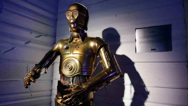 C-3PO would be in the middle of the uncanny valley graph, since he's built like a person but not nearly mistakable for human. Daniel Boczarski/WireImage/Getty Images