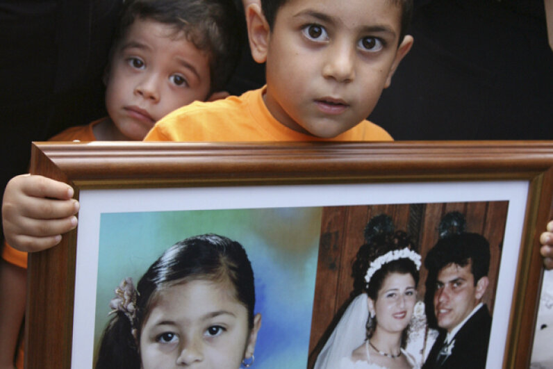 In 2007, 4-year-old Vassilis Koutsoftas held a large frame containing photos of his parents and sister, who were killed in the Helios air crash north of Athens two years earlier. © ANDREAS MANOLIS/Reuters/Corbis