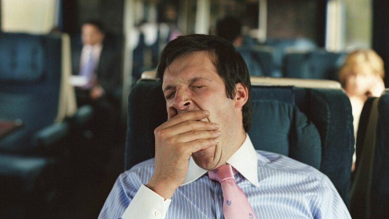 businessman yawning on train