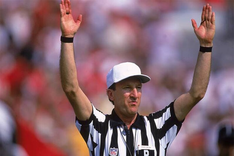 "Referee Phil Luckett signals a score during a game between the Minnesota Vikings and the Tampa Bay Buccaneers in 2000. Back in 1998, he heard the Pittsburgh Steelers co-captain call ""heads"" on a pre-game coin toss. Everyone else heard ""tails."" Andy Lyons/Allsport/Getty Imges"