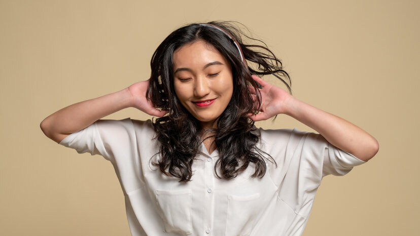 Young Asian woman listening to headphones