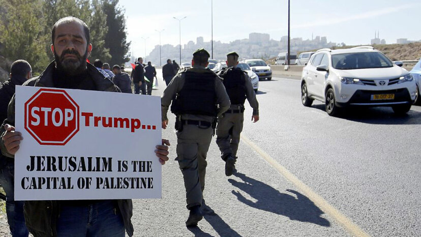 A Palestinian protester holds a placard during a demonstration against the construction of Jewish settlements in the occupied West Bank and against President Donald Trump.  BBAS MOMANI/AFP/Getty Images