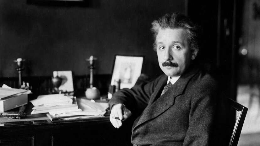 Albert Einstein sits at his desk.