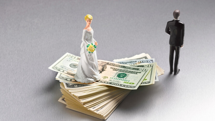 bride figure on top of pile of dollar bills