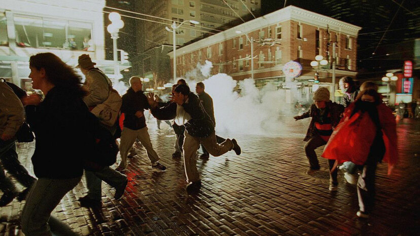 Anti-WTO protestors run from exploding tear gas grenades as riot police continued to battle World Trade Organization demonstrators during the Battle in Seattle, December 1999. KIM STALLKNECHT/AFP/Getty Images