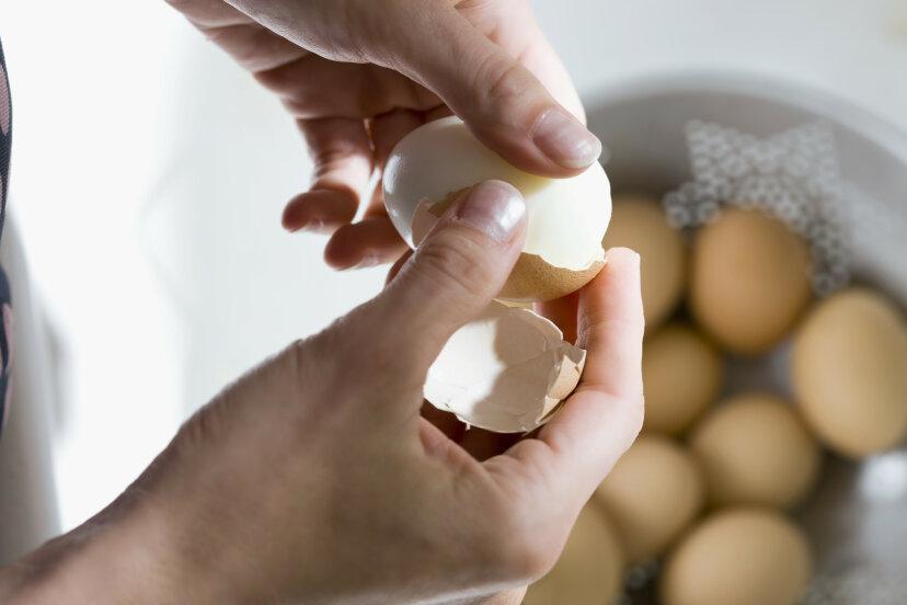 A woman peels a boiled egg.