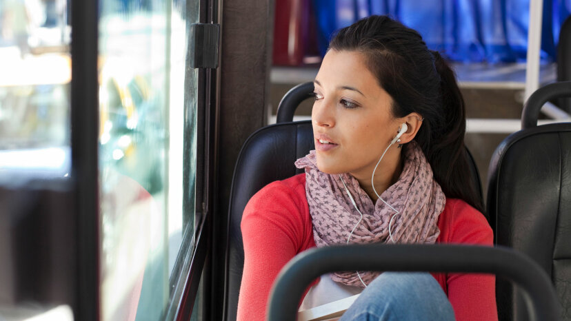 Indian woman on bus with headphones