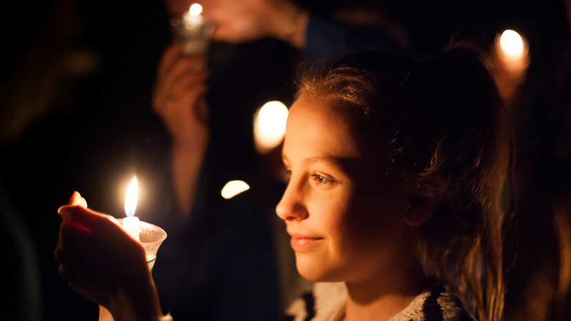 girl lights a candle during the Burns Night