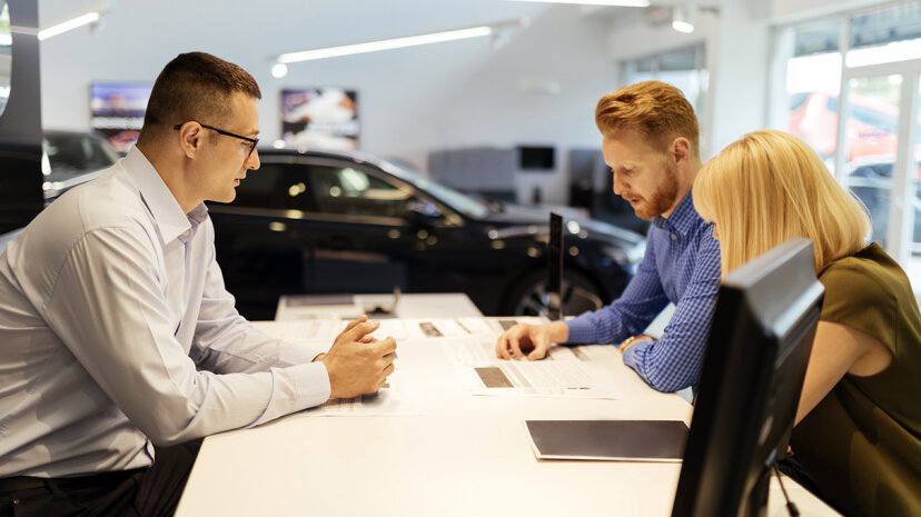Car salesperson and clients